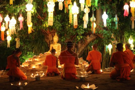 Thai monks meditate around buddha statue among many lanterns