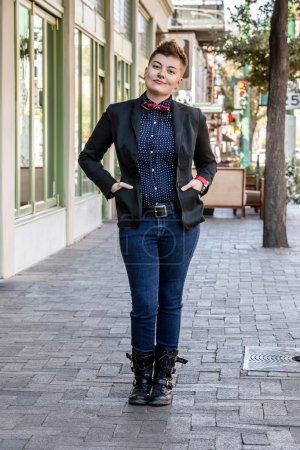Photo pour Dapper jeune femme fluide de genre sur le trottoir de la ville - image libre de droit