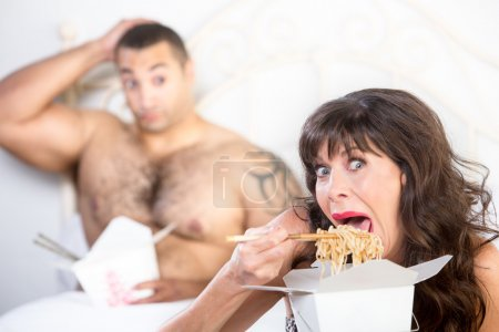 Photo for Mature woman sloppily eating Chinese food in bed with revolted handsome younger man - Royalty Free Image