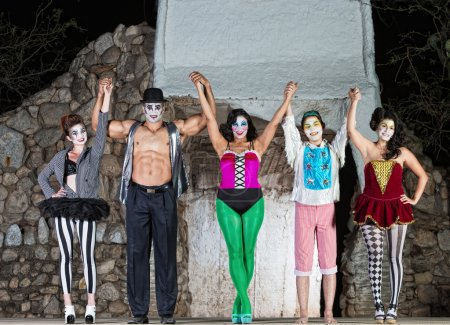 Photo pour Groupe de clowns heureux cirque tenant la main - image libre de droit