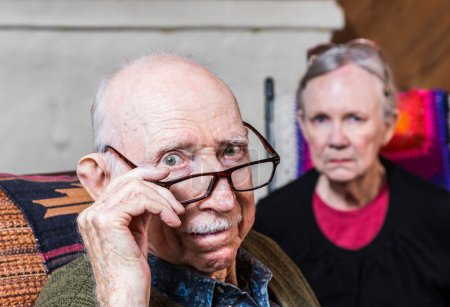 Photo for Concerned elderly couple sitting in livingroom scowling - Royalty Free Image