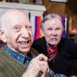 Angry old couple sitting indoors with scowling exp...