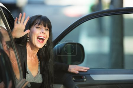 Photo for Attractive woman waving as she exits vehicle on downtown street - Royalty Free Image