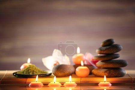 Photo pour Spa nature morte avec des pierres, des bougies et des fleurs dans l'eau sur la lumière floue fond - image libre de droit