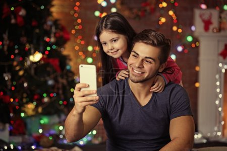 Photo pour Grand frère et petite soeur prise photo de leur auto avec un téléphone intelligent dans la salle de séjour de Noël - image libre de droit