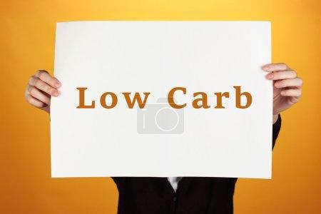Photo pour Femme tenant du papier avec du texte Low-Carb sur fond de couleur - image libre de droit
