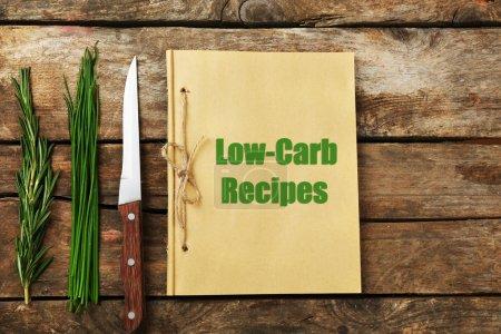 Photo pour Texte Low-Carb recettes dans le livre de recettes sur fond en bois - image libre de droit