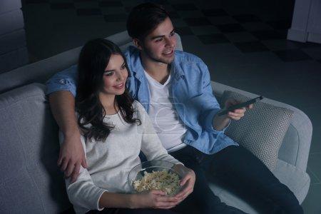 Photo pour Jeune couple regarder la télévision en soirée sur le canapé à la maison - image libre de droit