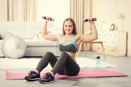 Sportswoman doing exercises with dumbbells