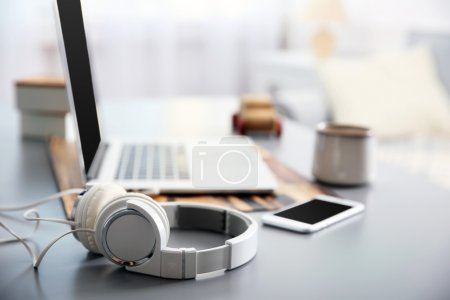 Photo for Headphones, phone and laptop on white table against defocused background - Royalty Free Image