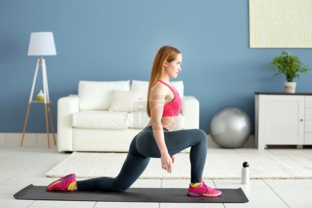 Sportswoman doing exercises on a mat