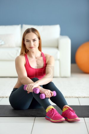Sportswoman sitting with dumbbells