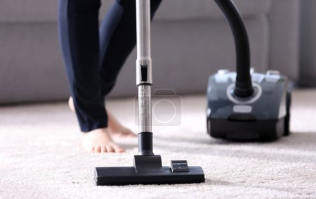 Woman using vacuum cleaner on carpet at home in th...