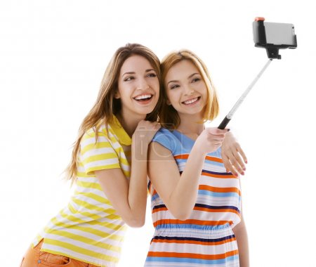 Two young women taking selfie with mobile phone is...