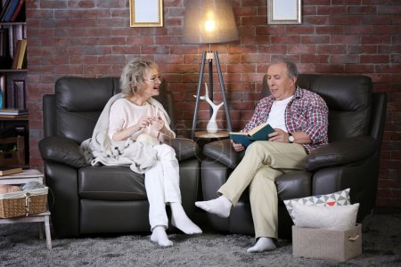 Photo for Mature couple talking and sitting close at home - Royalty Free Image