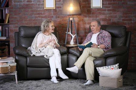 Photo pour Mature couple parler et assis à proximité à la maison - image libre de droit