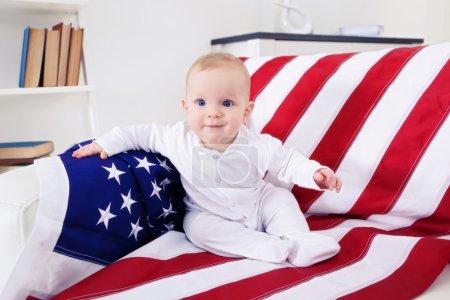 Cute baby boy on American flag