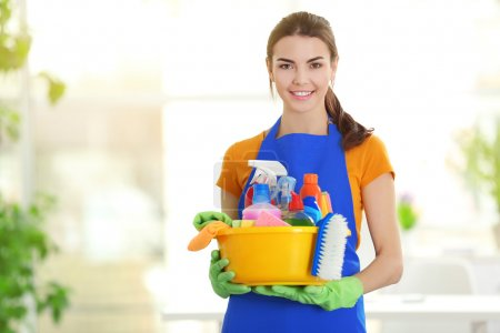 Photo for Woman in rubber gloves holding basin with detergents on blurred background - Royalty Free Image