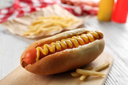 Hot dog with fried potatoes on craft paper