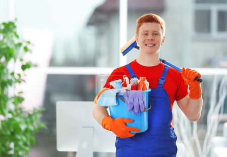 Young janitor holding cleaning products