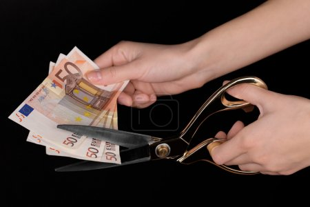 Hands with scissors cutting Euro banknotes