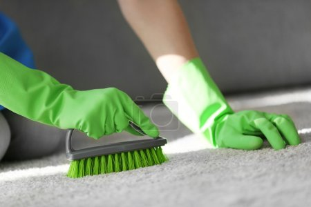 woman cleans carpet in room
