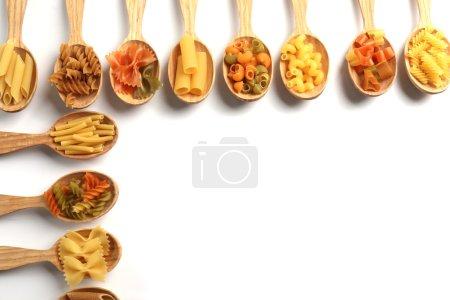 Photo pour Différents types de pâtes sèches en cuillères en bois sur fond blanc - image libre de droit