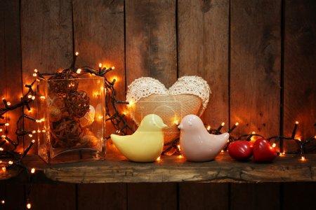 Photo pour Oiseaux en céramique et guirlande lumineux sur fond en bois - image libre de droit