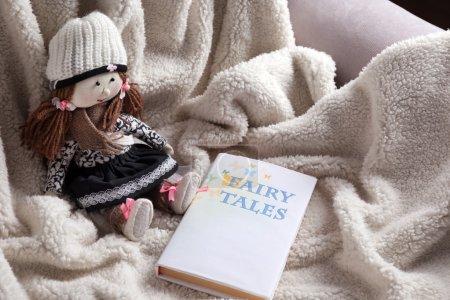 Photo pour Poupée Rag avec livre de contes de fées sur couvre-lit. Concept d'enfance - image libre de droit