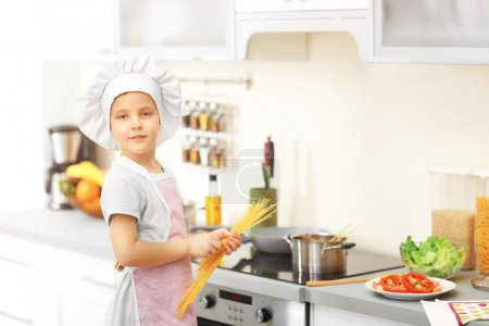 Photo for Little girl cooking spaghetti on the kitchen - Royalty Free Image