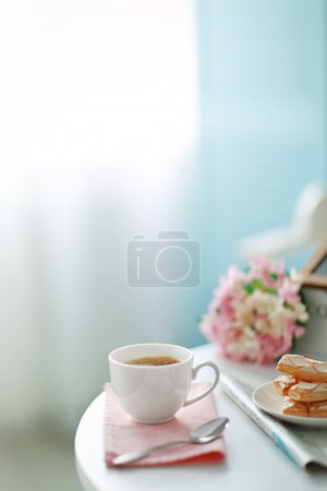 Cup of coffee with cookies on white table in light...