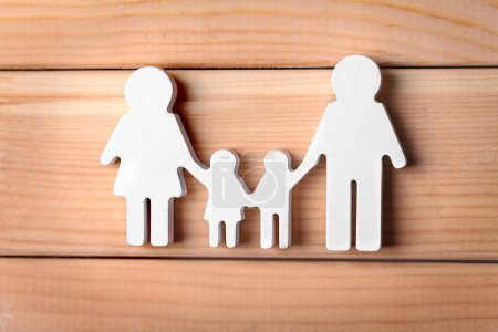 Photo for Cutout figurine of a family on wooden background - Royalty Free Image
