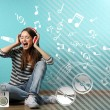 Young woman sitting on floor, listening to music a...