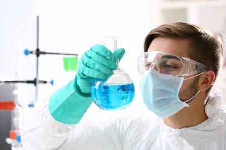 Man in checking test tubes