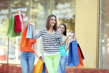 Photo pour Belles jeunes femmes avec des sacs à provisions dans la rue de la ville - image libre de droit