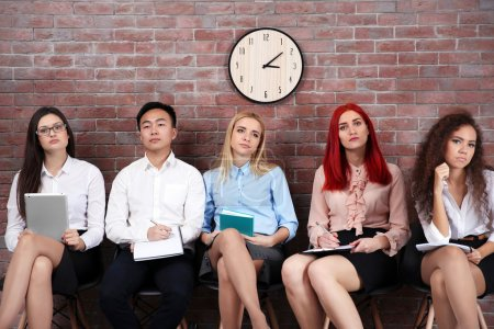 Photo for Young people sitting on a chairs in brick wall hall - Royalty Free Image