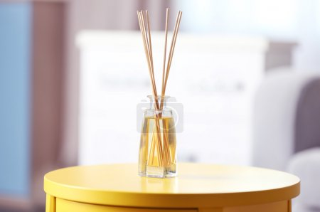 Photo for Handmade reed freshener on yellow table in living room, close up - Royalty Free Image