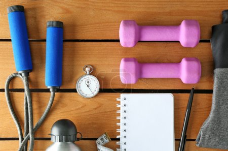 Photo for Athlete's set with female clothing, equipment, bottle of water and notebook on wooden background - Royalty Free Image
