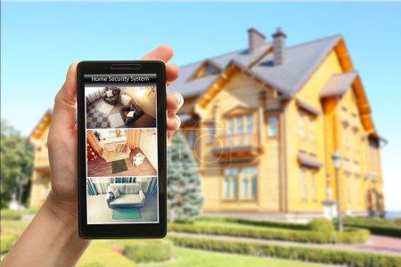 Photo pour Femme main tenant un smartphone sur fond de maison floue. Concept de système de sécurité à la maison - image libre de droit