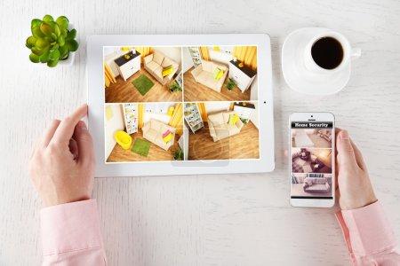 Photo pour Mains mâles avec tablette et téléphone sur le tableau blanc. Concept de système de sécurité à la maison - image libre de droit