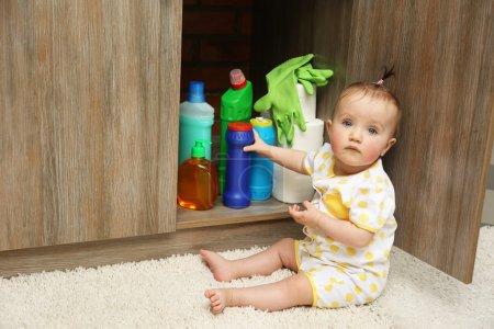 Photo pour Petite fille jouant avec des détergents dans la cuisine - image libre de droit
