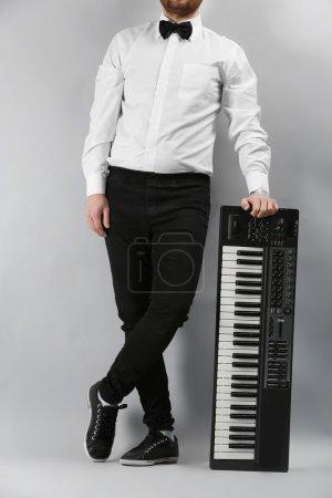 Photo pour Mains masculines avec synthétiseur sur fond de mur léger - image libre de droit