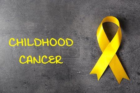 Photo pour Ruban jaune et texte Childhood Cancer sur fond texturé gris - image libre de droit