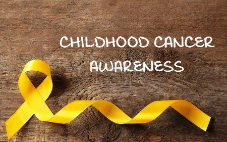 Photo pour Ruban jaune et texte de sensibilisation au Cancer infantile sur fond en bois - image libre de droit