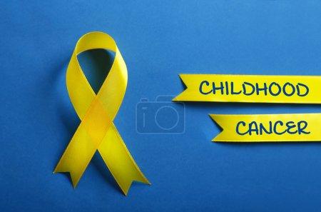Photo pour Ruban jaune et texte Childhood Cancer sur fond bleu - image libre de droit