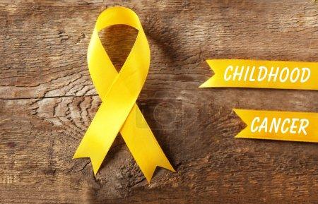 Photo pour Ruban jaune et texte Childhood Cancer sur fond en bois - image libre de droit