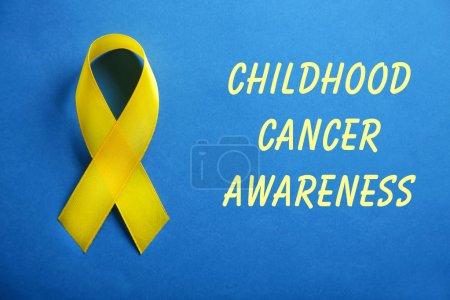 Photo pour Ruban jaune et texte de sensibilisation au Cancer infantile sur fond bleu - image libre de droit