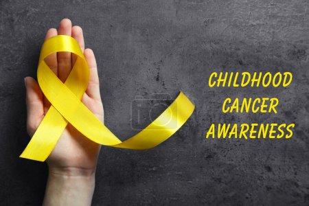Photo pour Main tenant le ruban jaune et texte de sensibilisation au Cancer infantile sur fond foncé - image libre de droit
