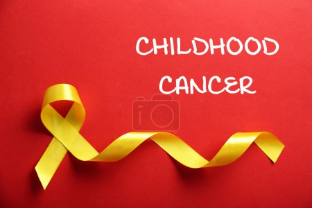Photo pour Ruban jaune et texte Childhood Cancer sur fond rouge - image libre de droit