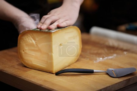Woman Tasting fresh cheese in cellar...